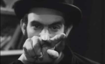 Black & white movie still of a man wearing a top hat and a cowl, glaring at the camera and pointing two creepy long fingers.